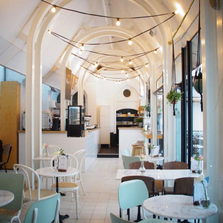 Grote witte ruimte met ronde bogen, ronde witte tafels en mintgroene stoeltjes