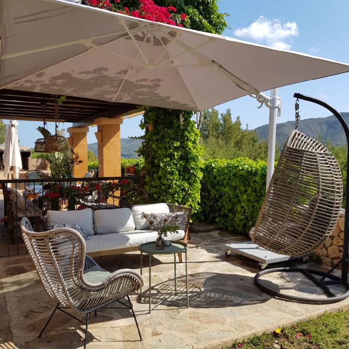 Loungestoelen en een hangstoel op een terras van een hotel op Ibiza
