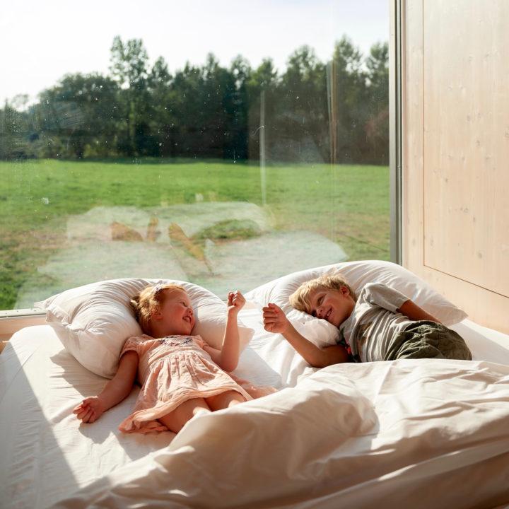 Twee kinderen in het grote bed voor het raam.