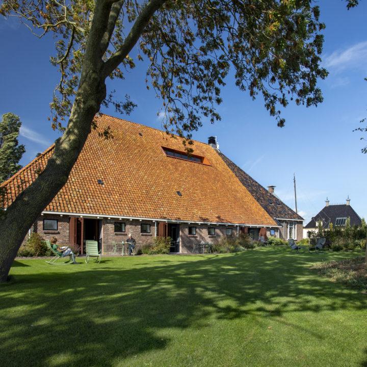 Zijkant van een boerderij in Friesland, met groen grasveld ervoor