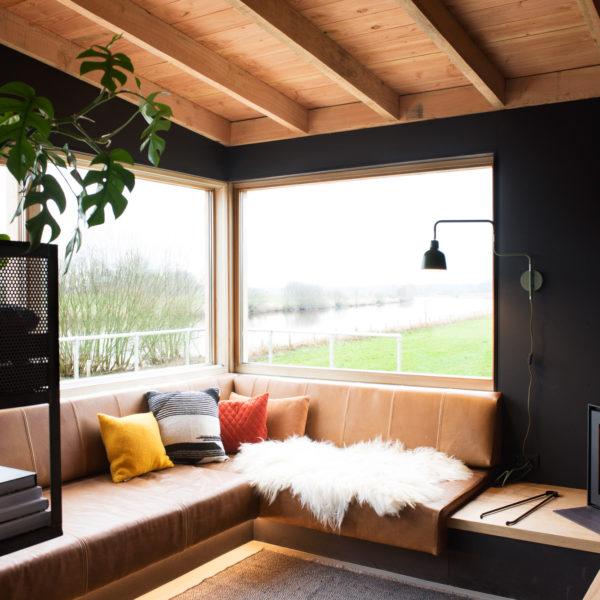 De woonkamer met loungehoek, houtkachel en grote ramen met uitzicht over de Vecht.