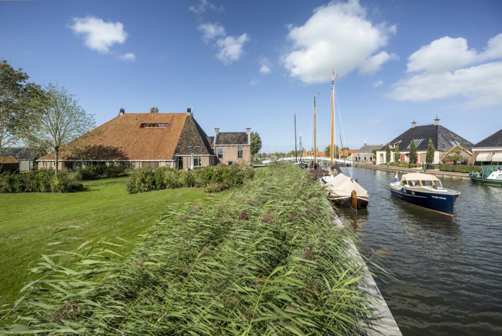 Grote Friese boerderij aan het water met bootjes in de vaart