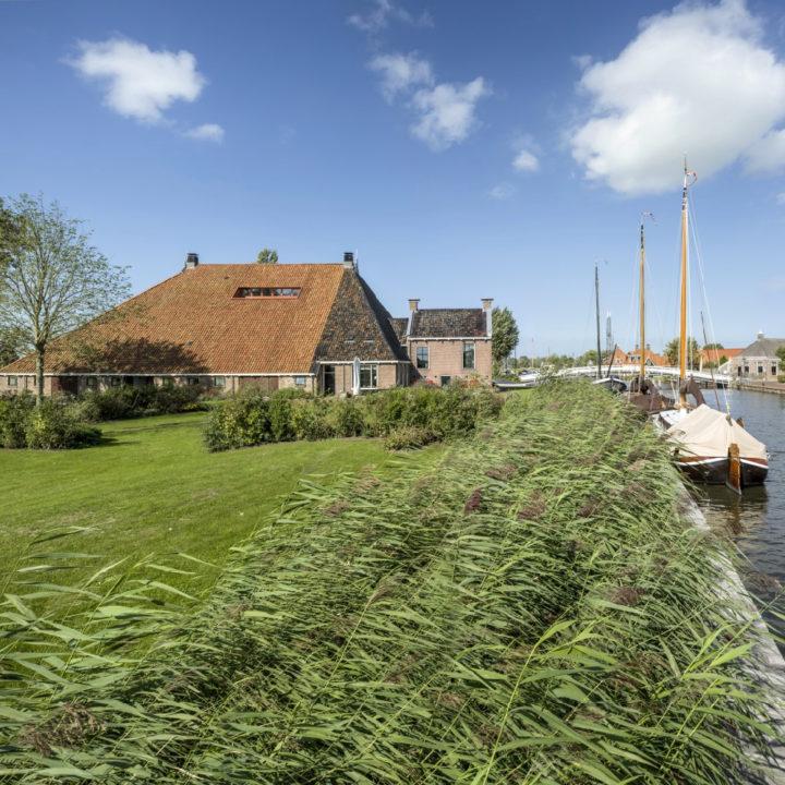 Grote Friese boerderij aan het water met bootjes aan de steiger