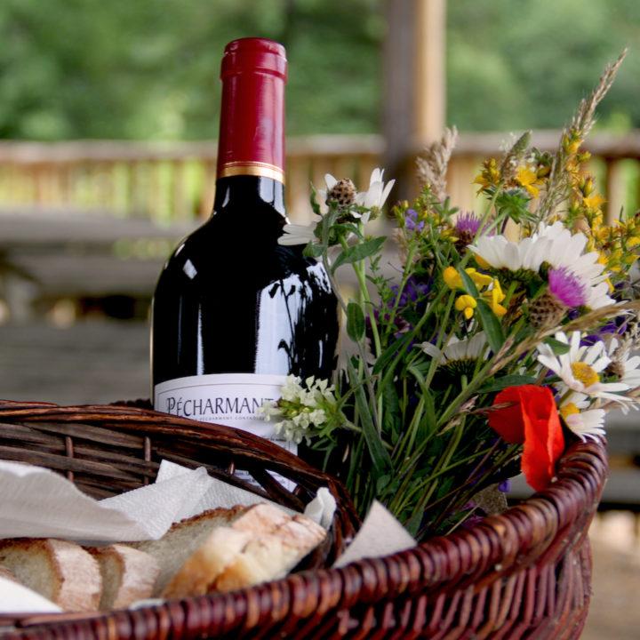 Mand gevuld met bloemen, wijn en stokbrood