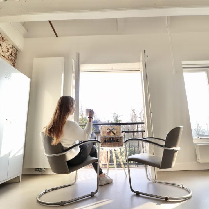 Meisje in een fauteuil voor het raam, bij een B&B in Dokkum