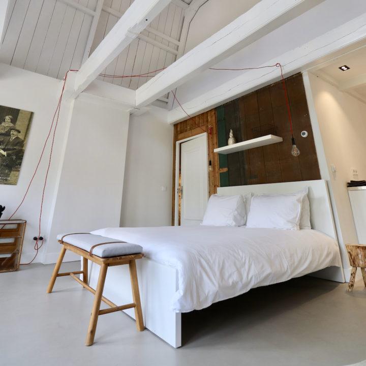 Witte slaapkamer met stoere balken, in een B&B in Dokkum