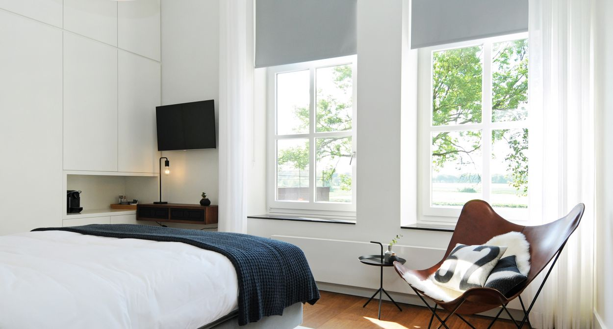 Lichte kamer met TV, nachtkastje, bed en een ligstoel