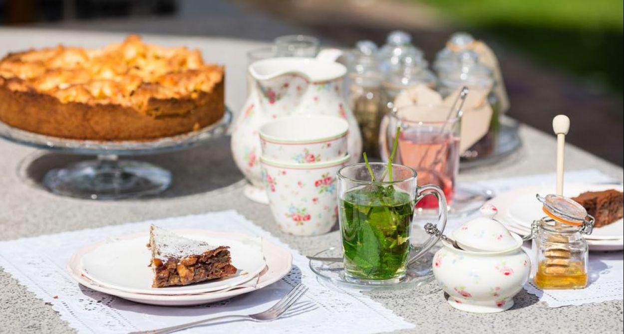 Mooi sfeerbeeld van tafel met taart en theeeservies en muntthee met potje honing