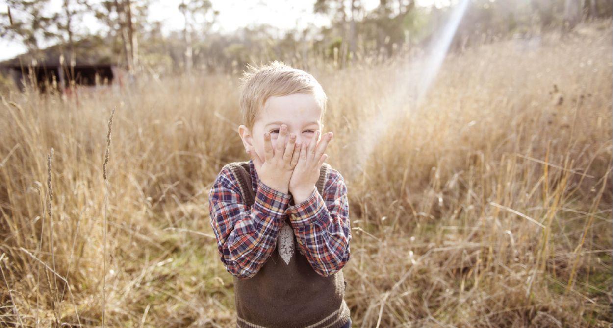 Een jongetje met een geruite blouse, in een weiland vol hoog geel gras en een zonnestraal. Jongetje slaat zijn handen voor zijn mond