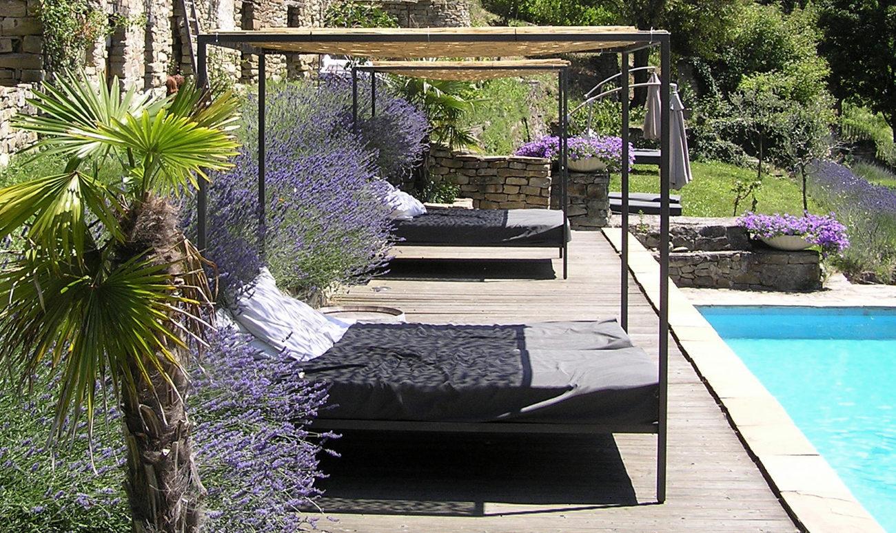 Loungebedden naast zwembad op houten deck met mooie planten en bloemen