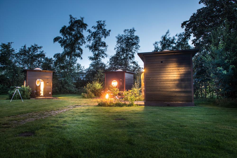 Een bijzonder adres voor je vakantie in Twente: slapen in een Sterrenkubus. Prachtig verlicht in de schemering.