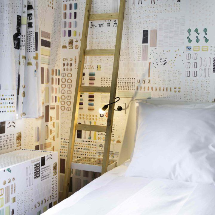 Bed met wit beddengoed en trapje als nachtkastje en vrolijk behang op de wanden