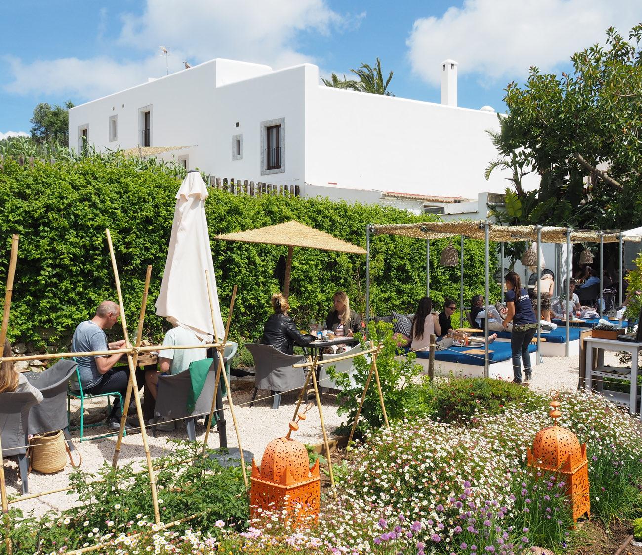 Terras met loungeplekken en tafels waar mensen aan het eten zijn in bloementuin