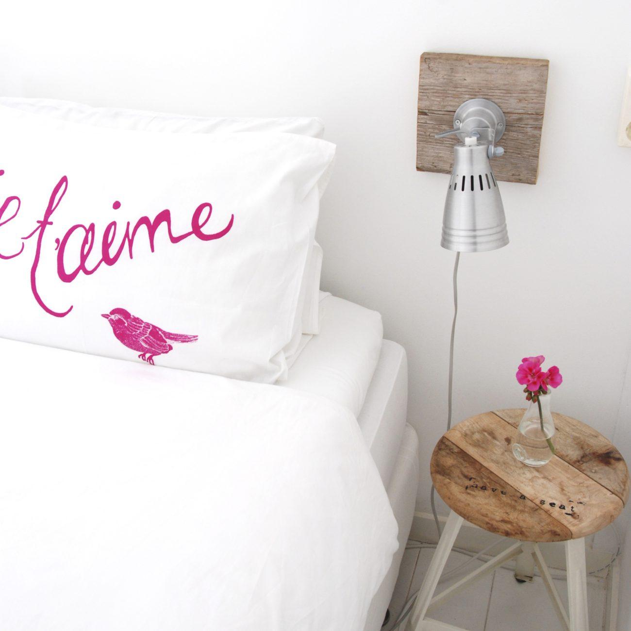 Bed met wit beddengoed met witte omgeving en hout accenten