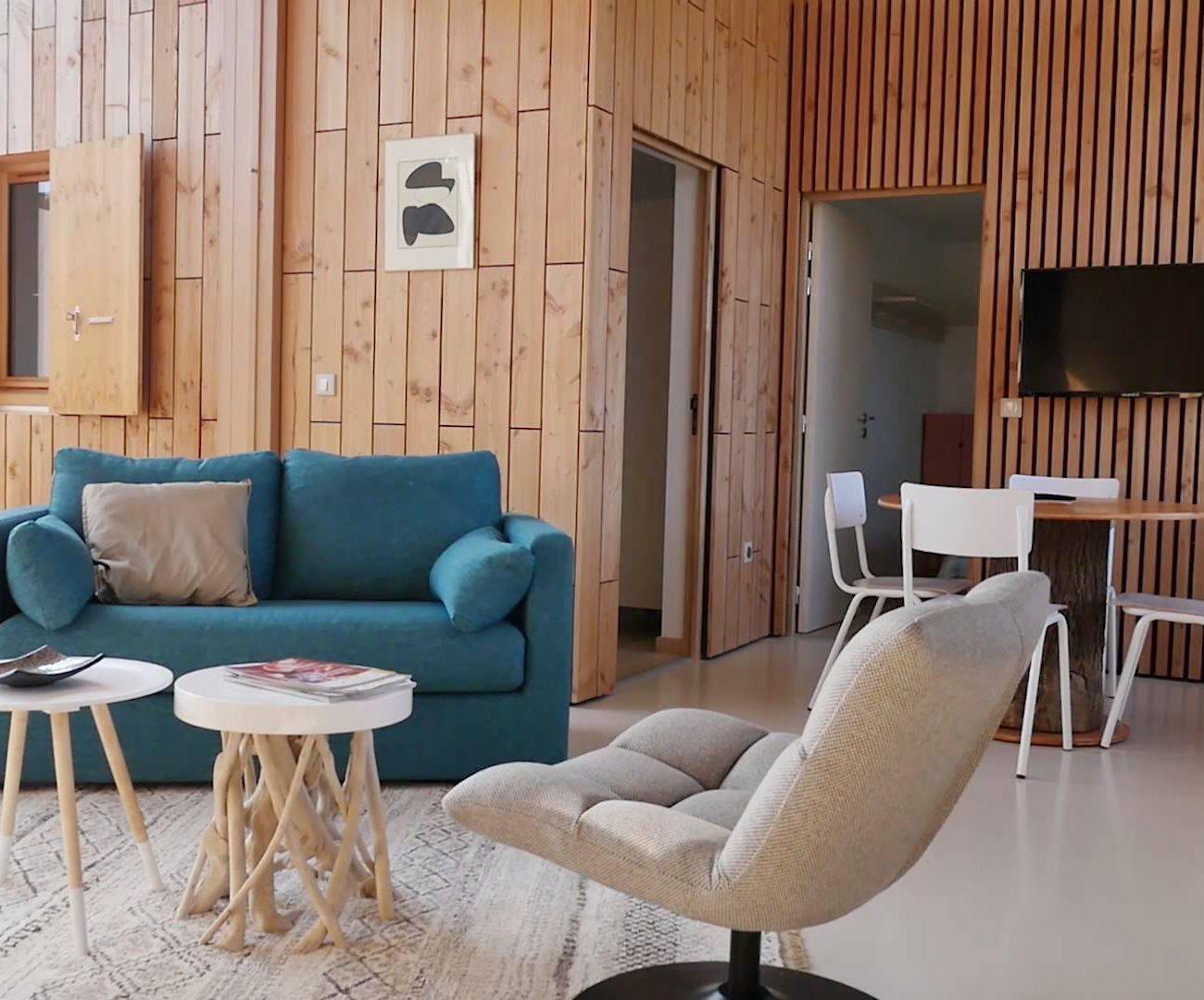 Woonkamer met fauteuil en blauwe bank van vakantiehuis