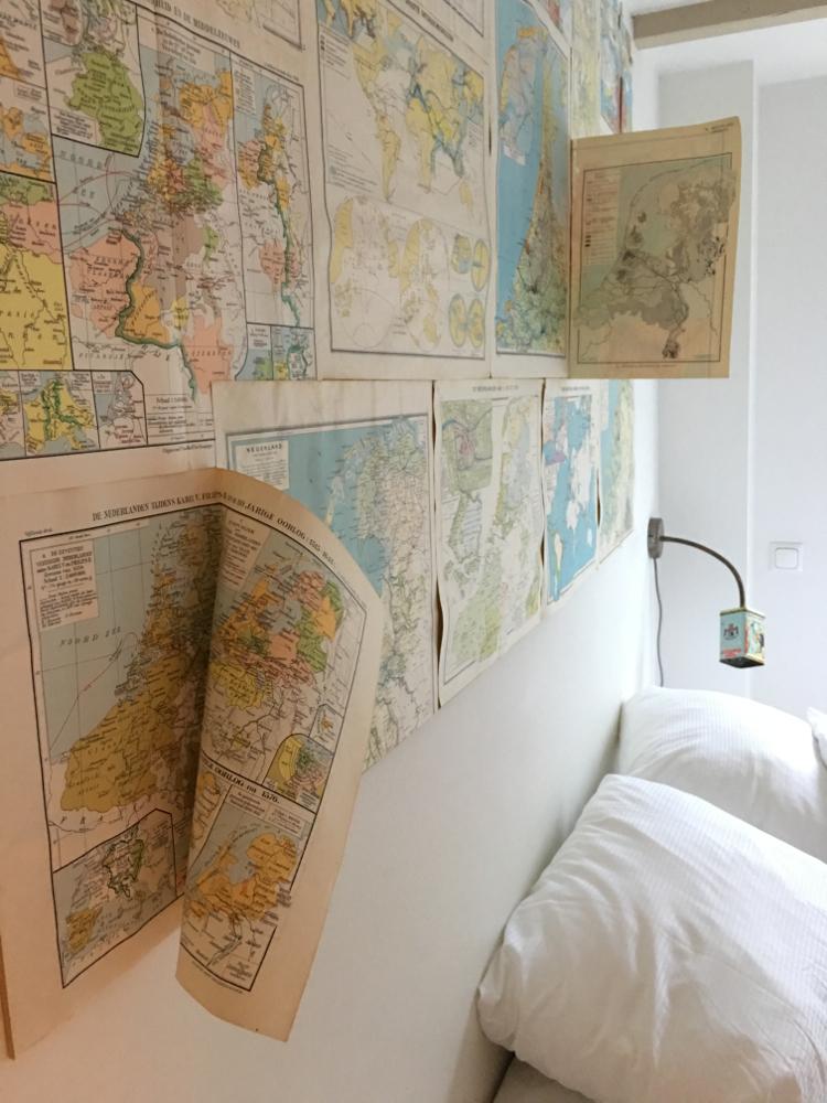 een twee persoons bed in een van de gastenkamers van Hello I'm local. Met landkaarten boven het bed