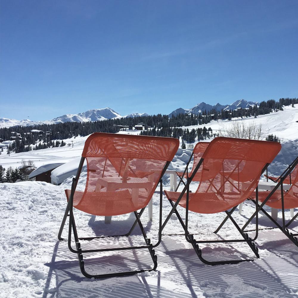 Rode ligstoelen in de sneeuw