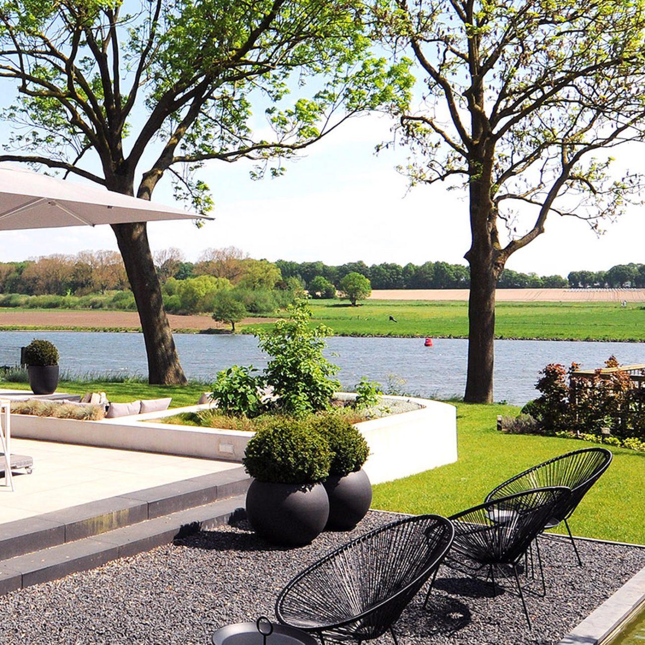 Tuin aan de Maas, met zwarte stoelen in het grind, een witte parasol en plantenbakken
