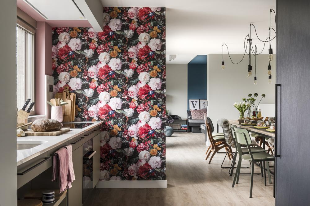Bijzonder vakantiehuis met open keuken en lange tafel. Op de wand bloemenbehang