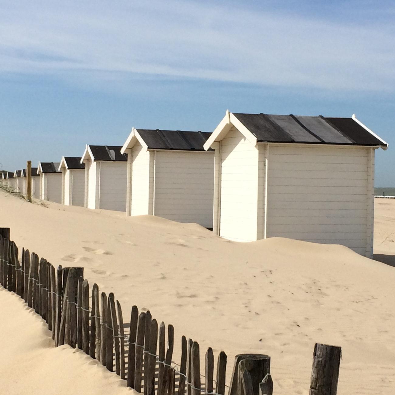 Een rijtje met witte strandhuisjes in het mulle zand. Op het strand bij Groede in Zeeland.