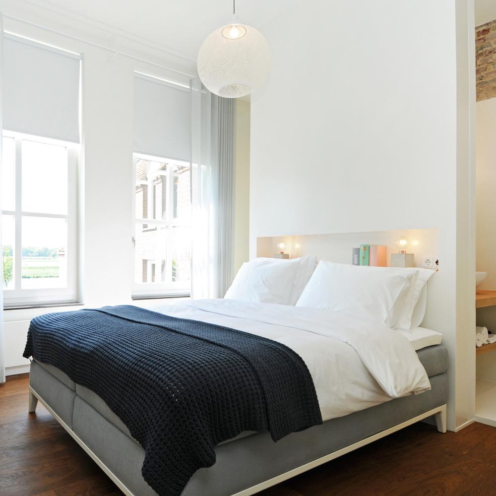 Luxe B&B kamer met groot tweepersoons bed voor hoge ramen, wit beddengoed en zwarte sprei