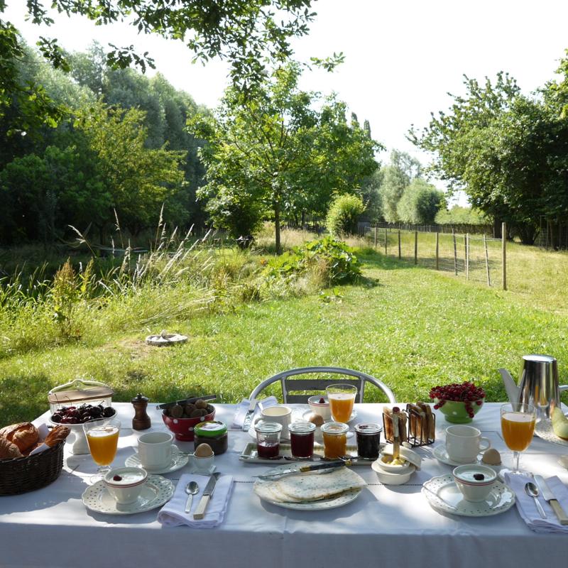 Een gedekte ontbijttafel met wit tafellinnen aan de rand van een weiland. Verse jus d'orang, brood op tafel, jam en mooi servies