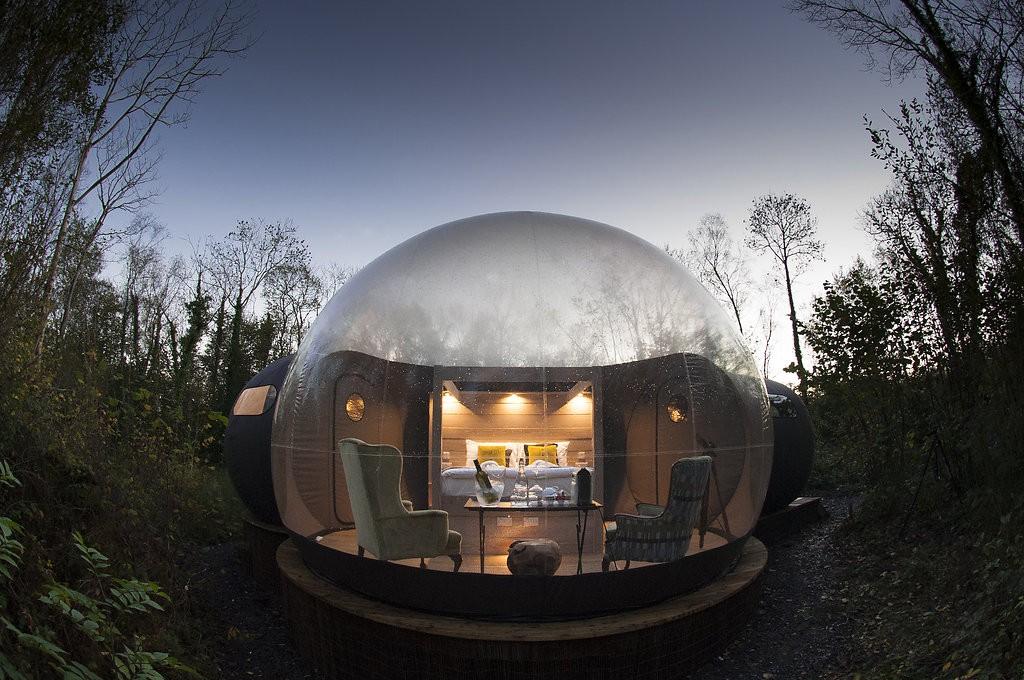 Een bubble tent met tweepersoons bed, luxe fauteuils en verlichting. In de schemering.