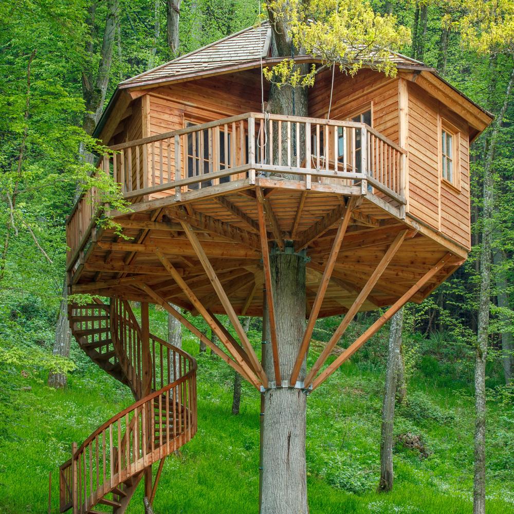 Een grote boomhut op een heuvel. Met wenteltrap en grote veranda