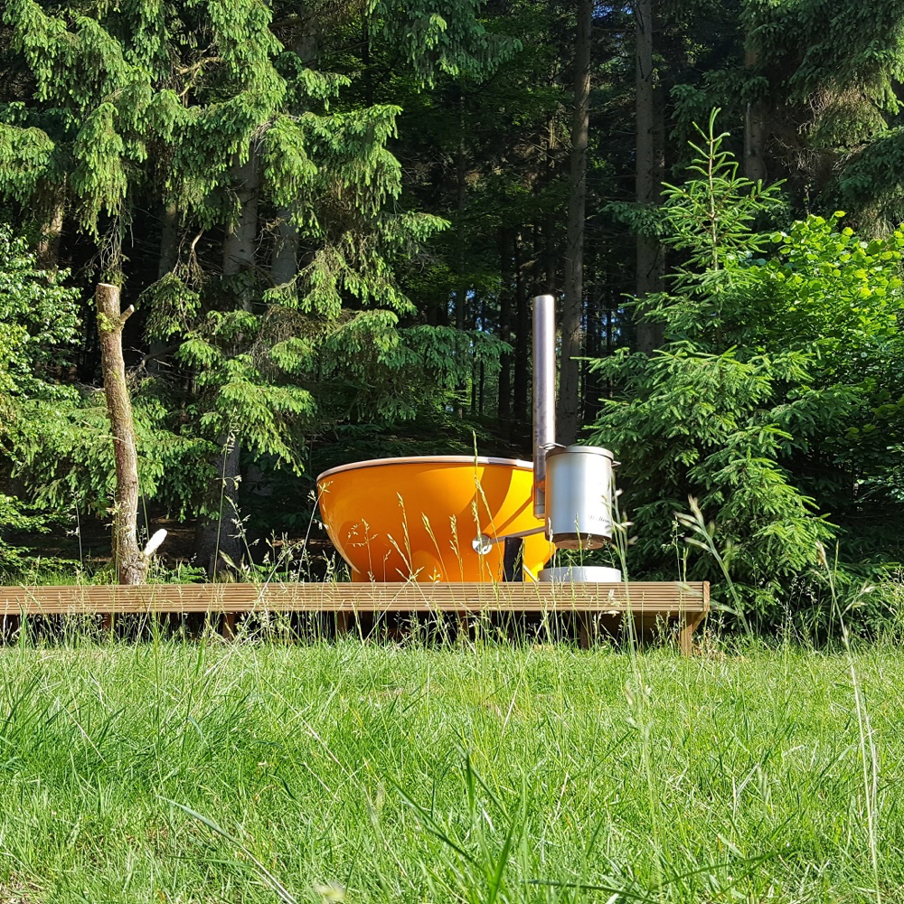 Een oranje hot tub in het gras, aan de rand van de Veluwe