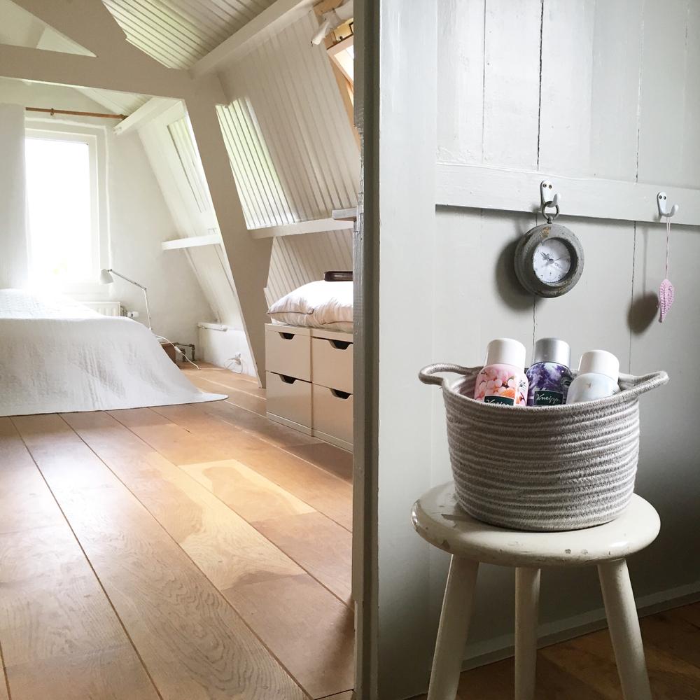 Een romantisch vakantiehuisje in Zeeland. Krukje met een mandje badspullen en doorkijkje naar tweepersoons bed in het wit