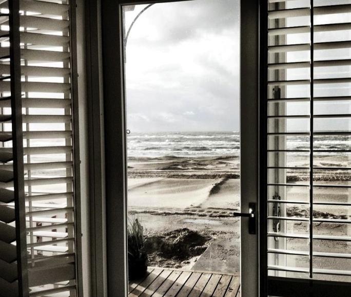 Een zwart-wit foto van een uitzicht over strand en zee vanuit een strandhuisje