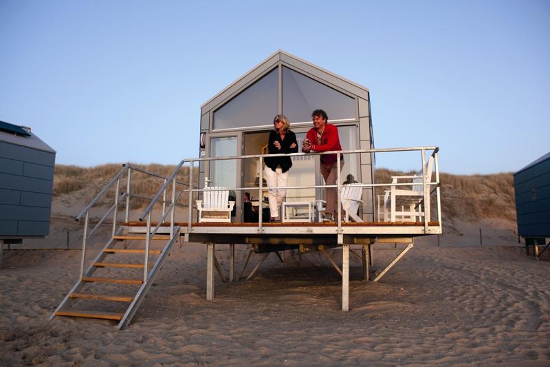 Twee mensen staan op de veranda van een strandhuisje te genieten van de zonsondergang.