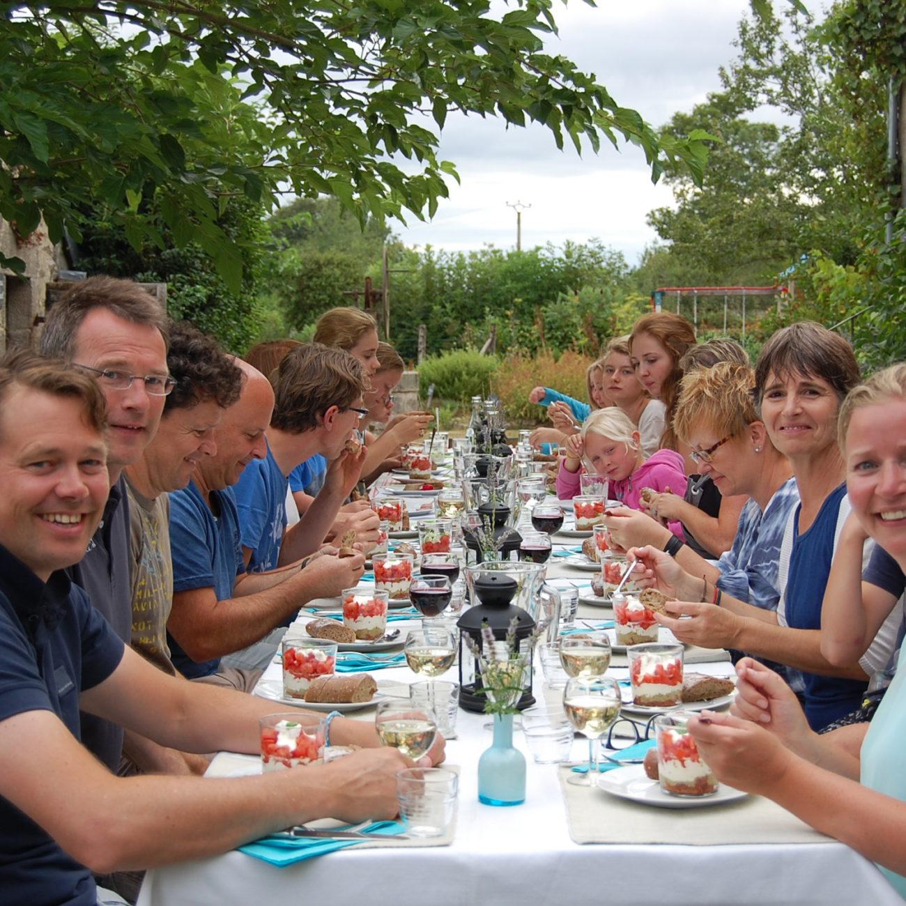 Lange tafel vol blije gasten tijdens de table d' hote.