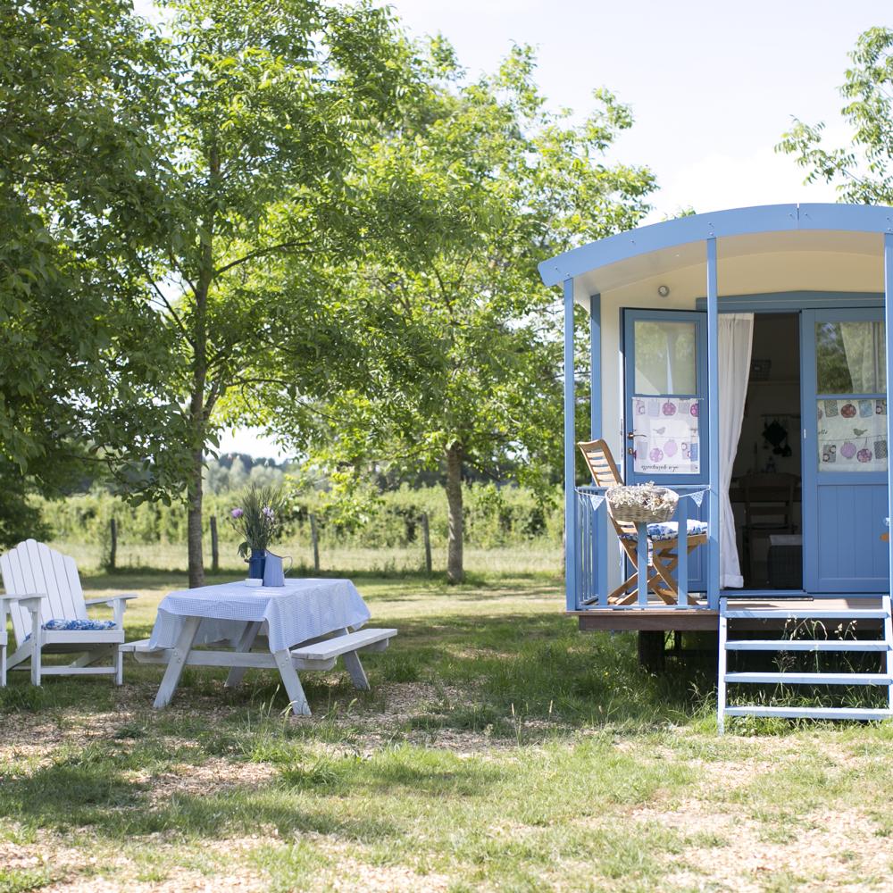 Glamping in een pipowagen. Een mooie blauw wit geschilderde, met bijpassende picknicktafel