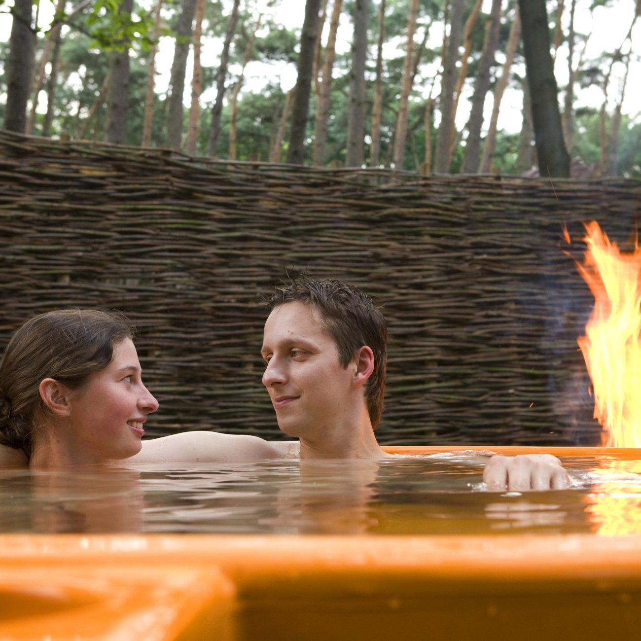 Een stel in een oranje dutch tub met brandend vuur