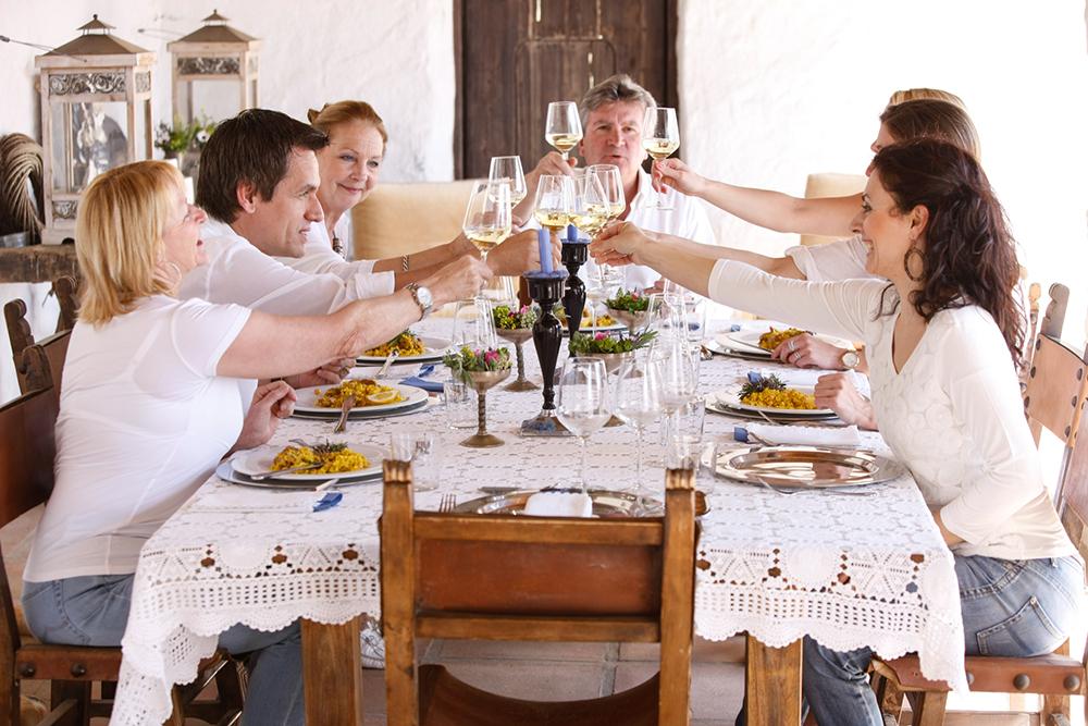 Een tafel met wit kleed, gevulde borden en mensen die samen proosten met glazen wijn.