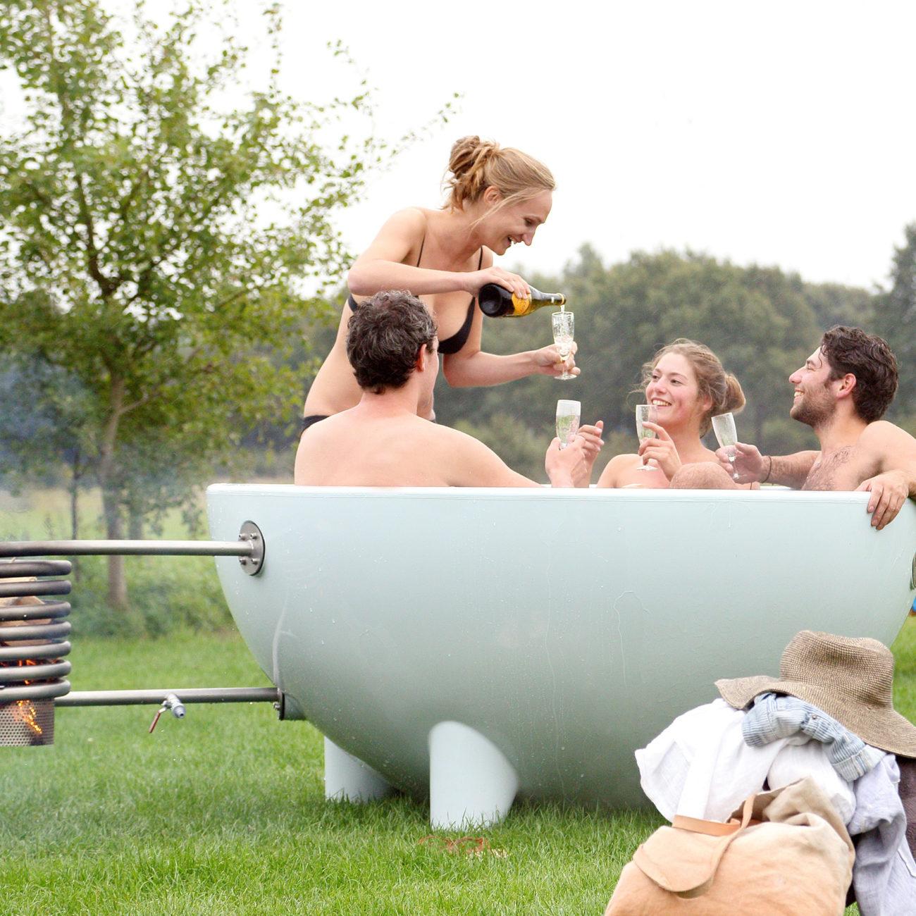 Twee koppels in een grijze dutch tub, een dame staat en schenkt glazen champagne in.