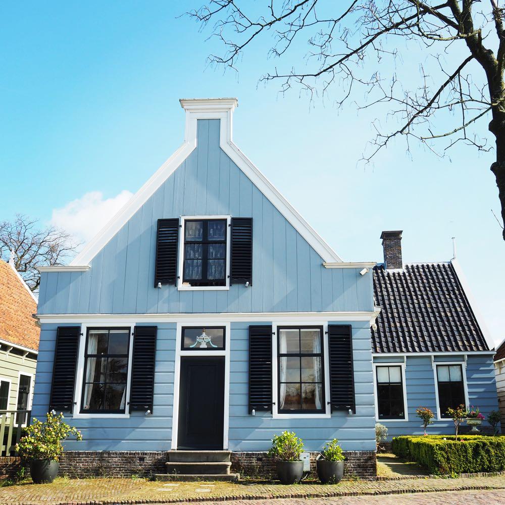 Een houten huis met lichtblauwe gevel in Broek in Waterland