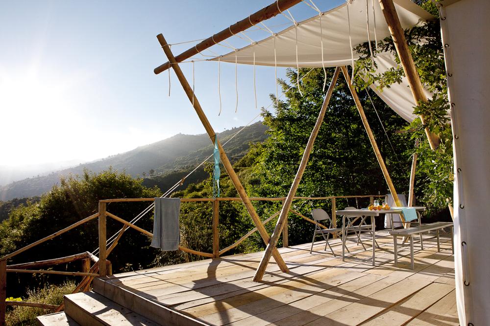 Een safari lodgetent met veranda en uitzicht over de groene heuvels