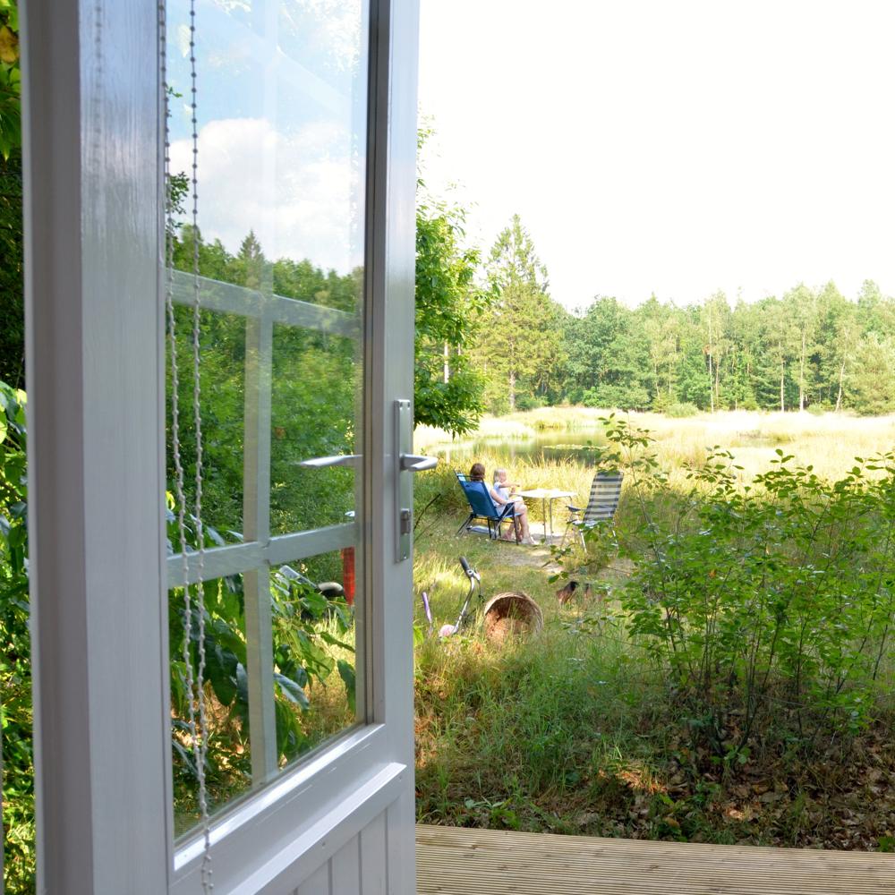 Een openstaande deur met uitzicht over de natuur, met daar middenin een stoeltje met vakantieganger