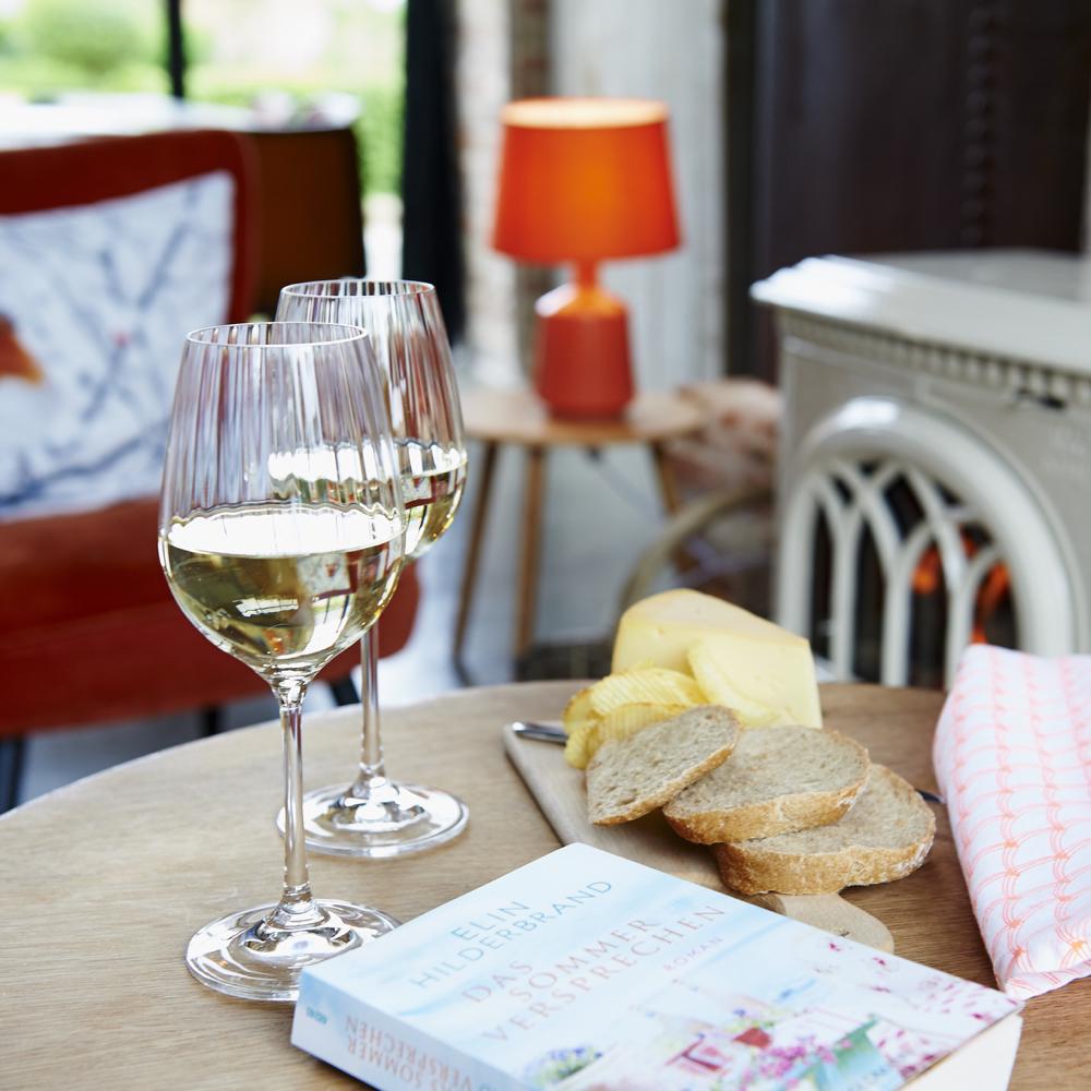 Wijnglazen met witte wijn en een plankje met brood op tafel. Een boek erbij