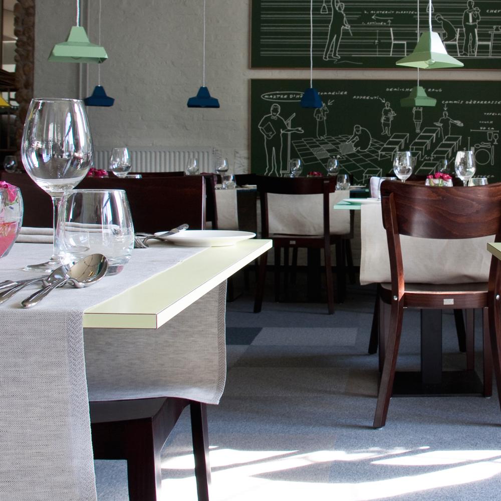 restaurant met verschillende tafels en een achterwand met groene tegels en krijtmuur