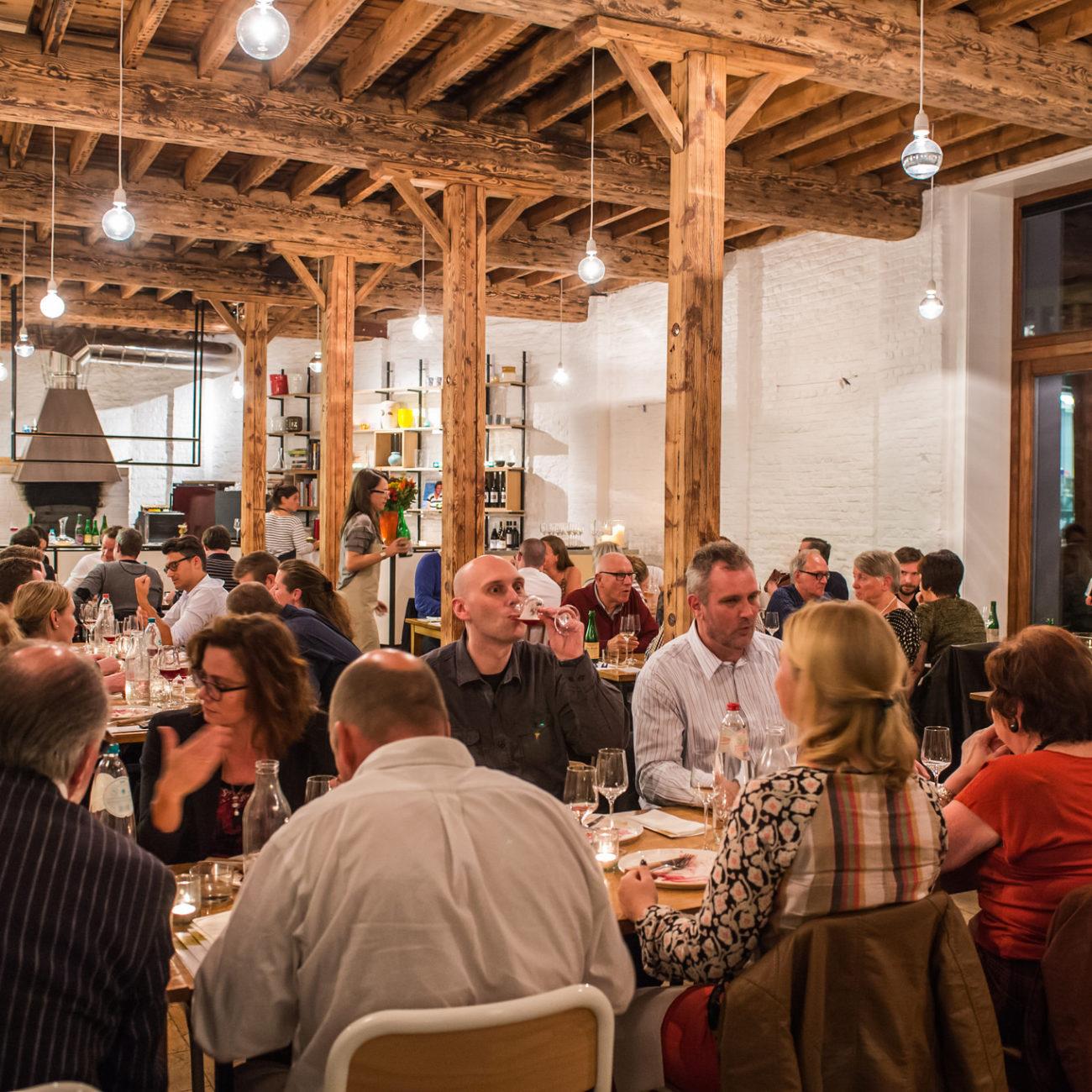 Een restaurant met lange tafels vol gasten. Stoere houten balken erboven