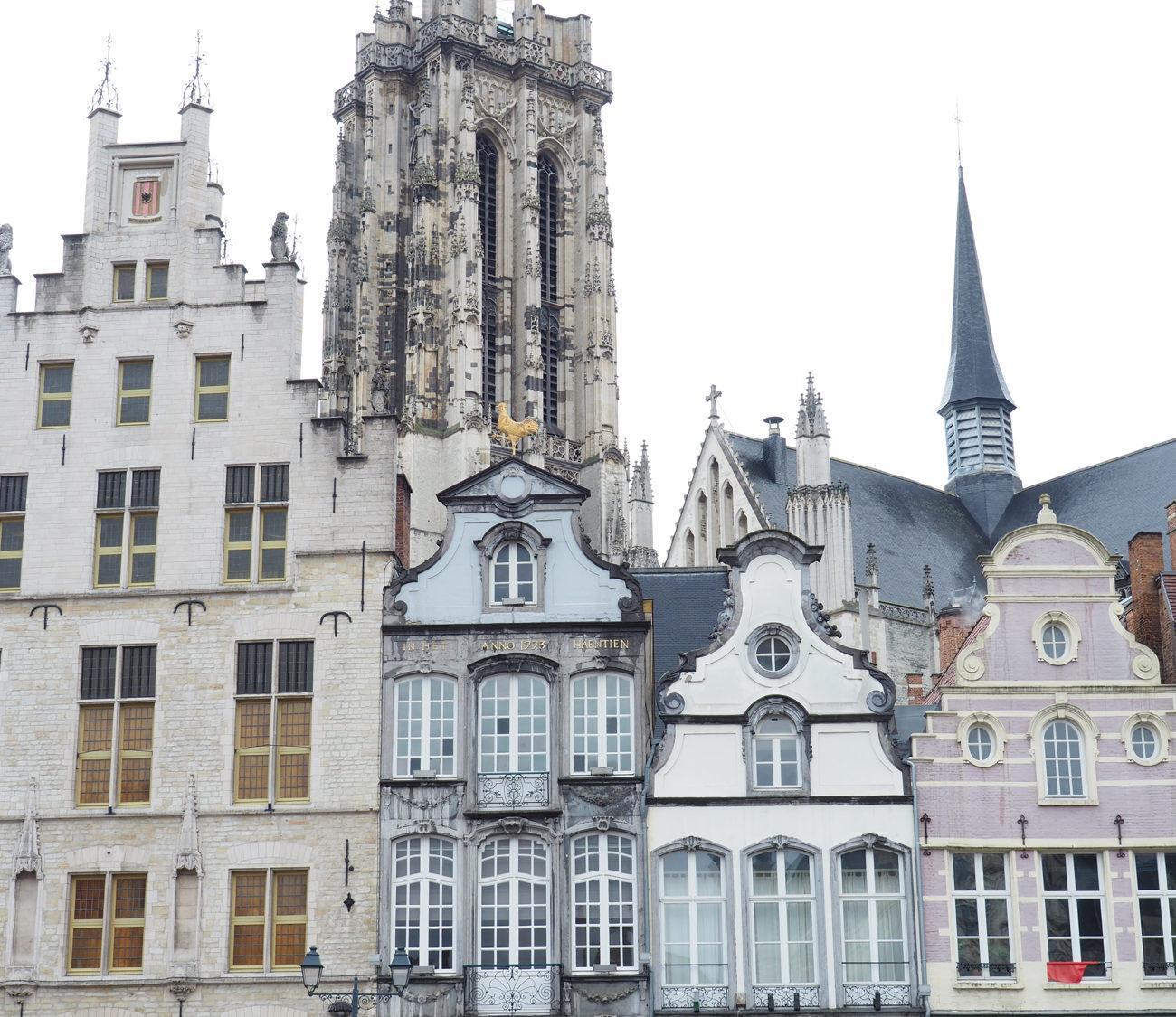 Historische gevels op de markt in Mechelen, met de grote kerktoren als achtergrond