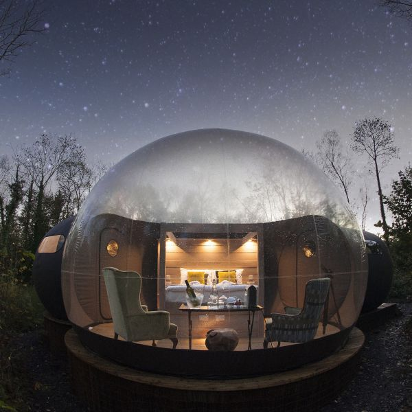 Een bubble tent by night. Doorzichtige ronde tent, luxe ingericht met goed bed voor een romantische vakantie