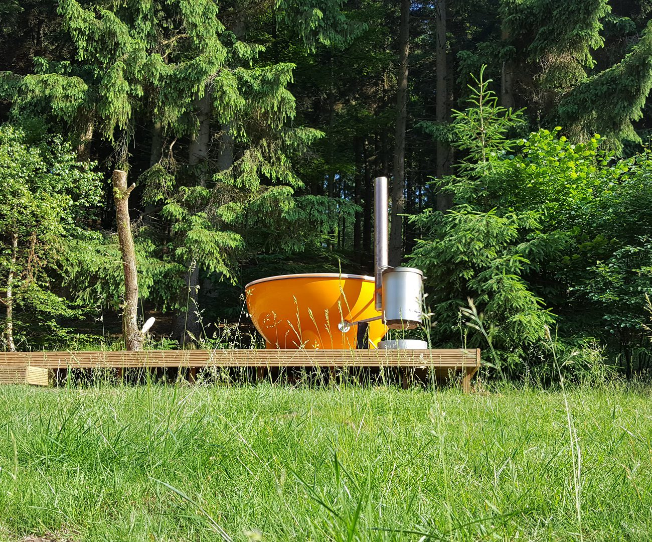 Een oranje hot tub/ dutch tub aan de rand van het bos