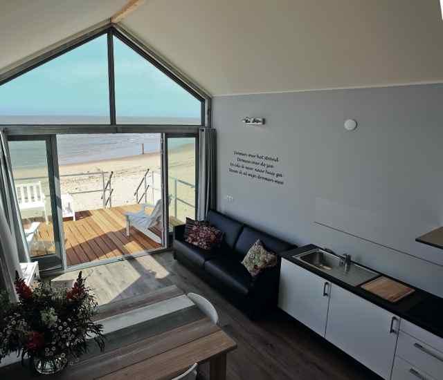 Het interieur van de strandhuisjes in Noord-Holland met een grote glazen gevel aan de strandkant. Een bijzonder plekje voor je vriendinnenweekend.