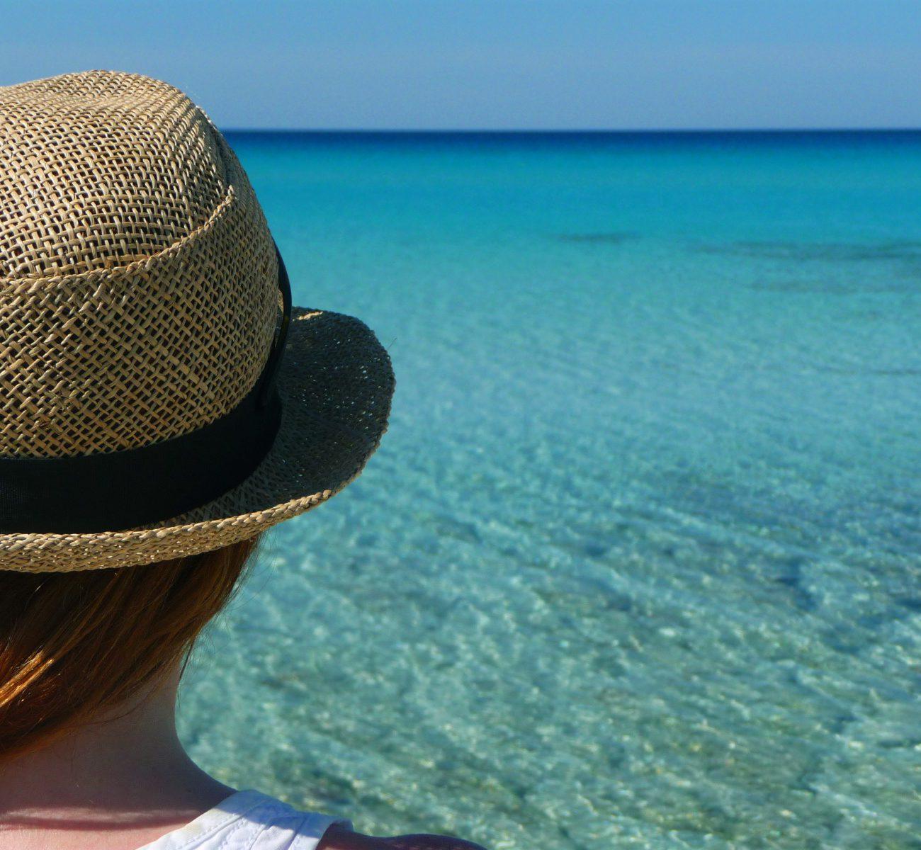 Een vakantieganger met rieten hoedje kijkt uit over het helderblauwe water.