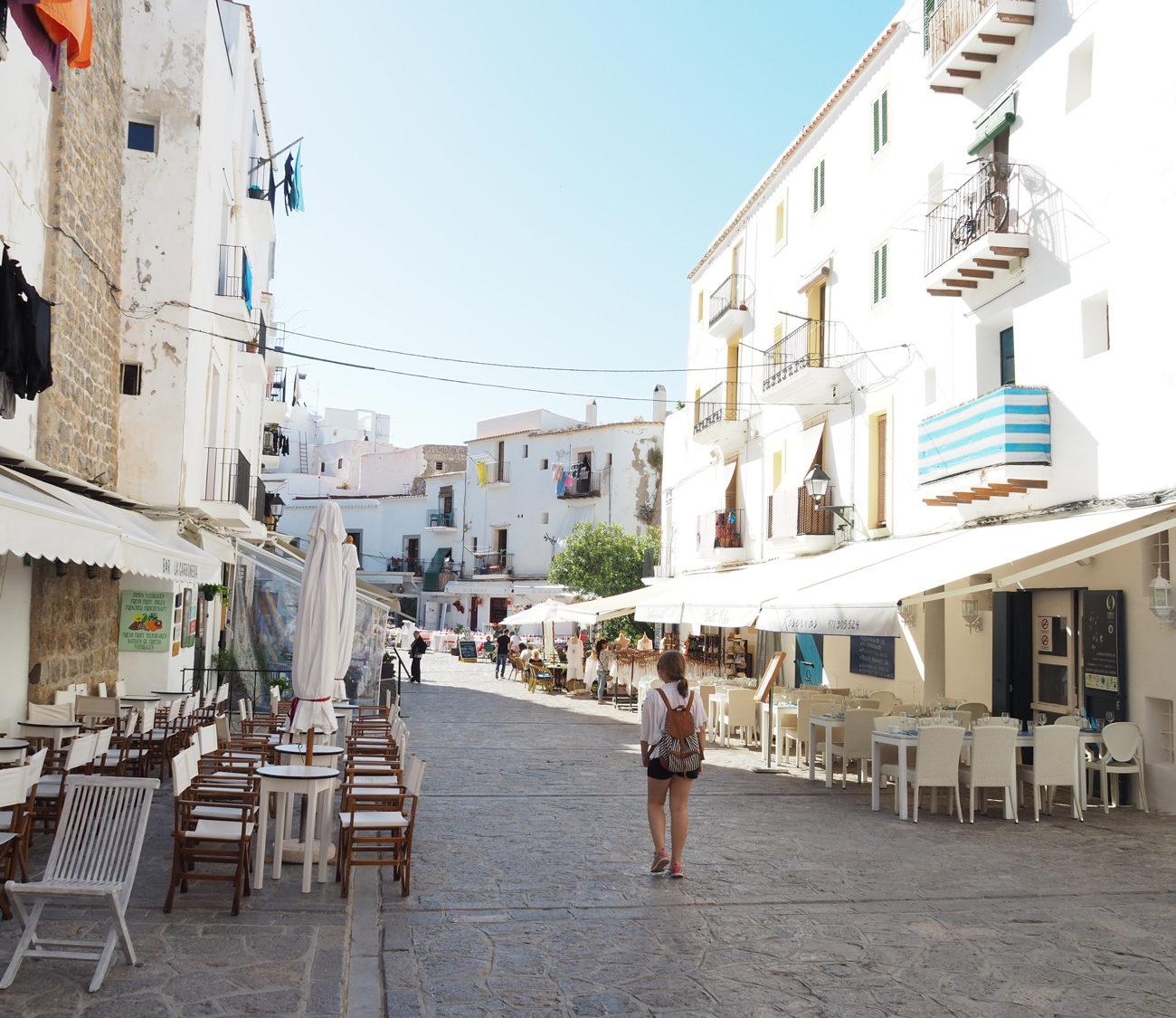 Een straat met witte huizen en vol terrasjes aan weerszijden van de straat.