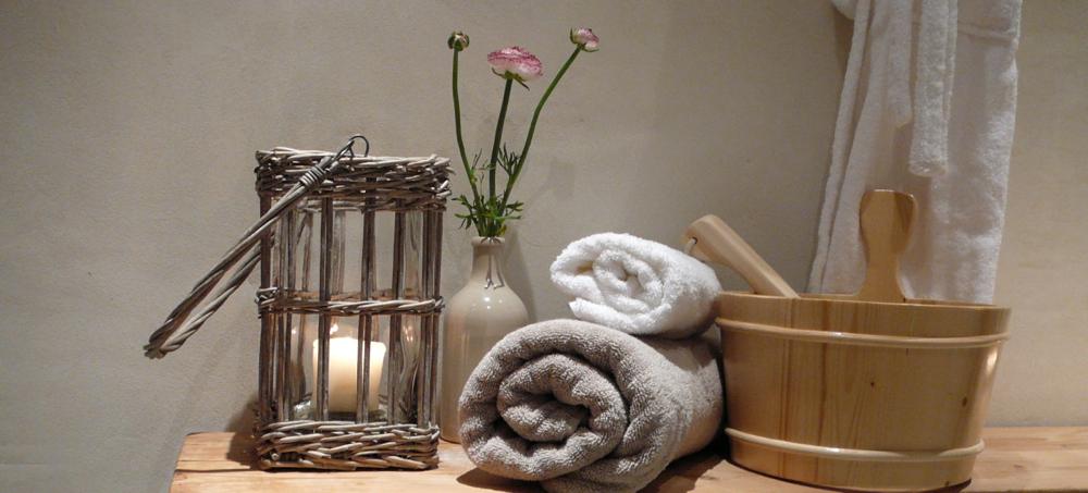 Een stapeltje opgerolde handdoeken met een houten tobbe en brandende kaas.